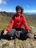 Young latin woman sitting doing yoga on a mountain top Royalty Free Stock Photography