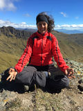Young latin woman sitting doing yoga on a mountain top Stock Images