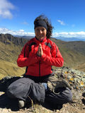 Young latin woman sitting doing yoga on a mountain top Stock Photo