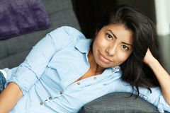 Young Latin woman smiling and relaxing on a sofa. Home royalty free stock photos