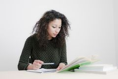 Young latin woman studying. In an empty room Stock Photography