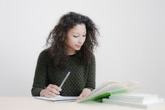 Young latin woman studying. In an empty room Stock Photos