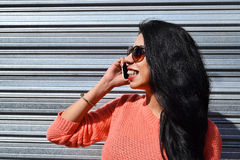Young latin woman talking on the phone Stock Photo