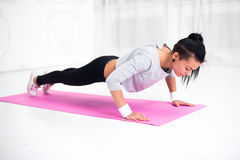 Young latin woman warming up and doing push ups at. Home fitness healthy lifestyle and diet concept royalty free stock photos