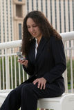 Young Latina Business Woman Messaging. Young Latina Business Woman Dialing Cell Phone Stock Image