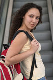 Young Latina Student with Backpack. Young Latina Student with holding a red backpack, looking over her shoulder in front of an escalator Stock Photos
