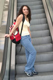 Young Latina student on escalator. Young Latina student on with red backpack riding an escalator Stock Images