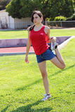 Young latina teen girl stretching on green grass. Young hispanic teen girl stretching leg shorts royalty free stock photos