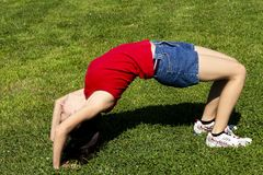 Young Hispanic Woman Bending Over Backwards On Green Grass. Young Latina Woman In Blue Shorts And Red Top Running Bending Over Backwards On Green Grass stock image