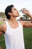 Young latino male athlete drinking water. On athletic field Stock Photography