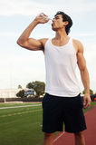 Young latino male athlete drinking water. On a track field Royalty Free Stock Photography