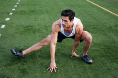 Young latino male athlete stretching. On athletic field Royalty Free Stock Photography