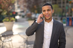 Young Latino man in city talking on cell phone Royalty Free Stock Image