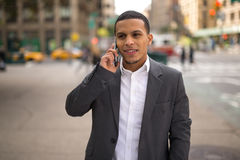 Young Latino man in city talking on cell phone Royalty Free Stock Photography