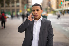 Young Latino man in city talking on cell phone Royalty Free Stock Images