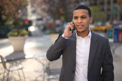 Young Latino man in city talking on cell phone Royalty Free Stock Photo