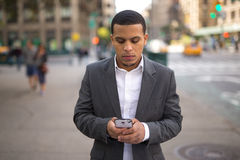 Young Latino man in city texting on cell phone Stock Photo