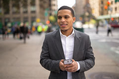 Young Latino man in city texting on cell phone Stock Images