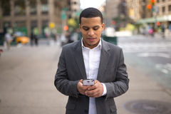 Young Latino man in city texting on cell phone Stock Photos