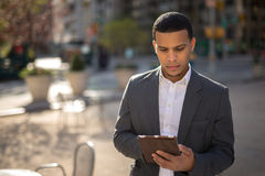 Young Latino man in city using tablet pc Stock Photography