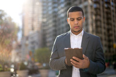 Young Latino man in city using tablet pc Royalty Free Stock Image