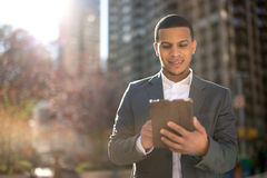 Young Latino man in city using tablet pc Stock Photos