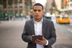 Young Latino man in city using tablet pc Royalty Free Stock Photo