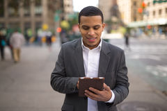Young Latino man in city using tablet pc Royalty Free Stock Images