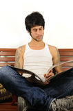 Young latino man reading. Portrait of young trendy hispanic man reading a magazine - isolated Royalty Free Stock Images