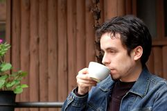 Young Latino Man Relax. A young man enjoys and having a cup of coffee at restaurant's terrace Stock Photos