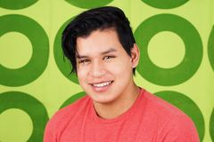 Young latino man smiling over green. Cute young latino man smiling over green Stock Photo