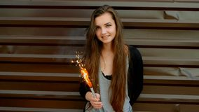 Young Latino women against brown wall with sparkler having fun.  stock footage