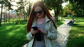 Young laughing adorable redhead student woman in coat holding her smartphone and texting posing outdoors on park path stock video footage