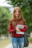 Young laughing adorable redhead student woman in red plaid jacket holding her papers posing outdoors on park path with blurred gre Royalty Free Stock Photography