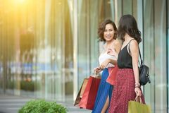 Happy female shoppers. Young laughing Asian women with shopping-bags leaving store Royalty Free Stock Photography