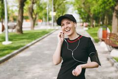Young laughing athletic beautiful brunette girl in black uniform and cap with headphones listening music, keeping hand royalty free stock photo