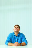 Young laughing businessman sitting at the table and looking up Royalty Free Stock Photography