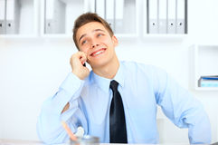 Young laughing businessman talking on cell phone Royalty Free Stock Photography