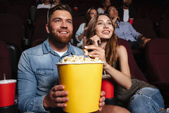 Young laughing couple holding a big popcorn bucket Royalty Free Stock Image