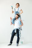 Young laughing couple holding paint rollers and looking at camera Royalty Free Stock Image
