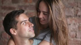 Young laughing couple hugging, having fun together, looking at camera
