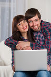 Young laughing couple using laptop while sitting on couch at hom Royalty Free Stock Photo