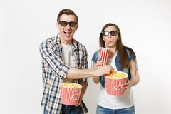 Young laughing couple, woman and man in 3d glasses watching movie film on date holding bucket of popcorn, plastic cup of. Young laughing couple, women and men in stock photo