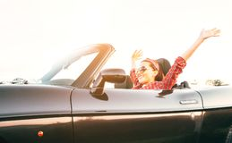Young laughing female cheerful rising hands up in by cabriolet car in sunny day time royalty free stock photo