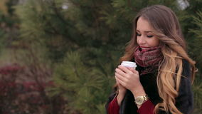 Young laughing girl with a cup of coffee for a walk in the park outdoors. stock video footage
