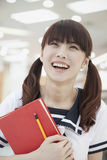 Young Laughing Girl in School Uniform with Notepad, Looking Up Stock Images