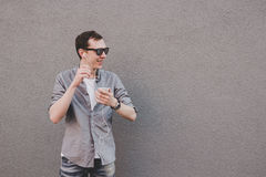 Young laughing hipster man using his smartphone, listening music. Gray background, copy space Royalty Free Stock Photos