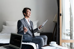 Young laughing male lawyer reviewing some documents. And contracts in a hotel room during a business trip Stock Photography