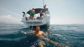 Tourist man swims for yacht. Split with underwater, real shoot. Slow motion. Young laughing men on sailing yacht. Split with underwater, real shoot stock video footage