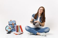 Young laughing smart woman student holding and using calculator solving math equations sitting near globe, backpack royalty free stock photo